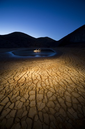 Dusk in a land of drought in the bottom of a dry tree in water photo