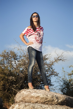 jeans girl: Young girl in shirt and jeans on upper rock
