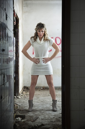 Sexy girl with expression of fear in abandoned building photo