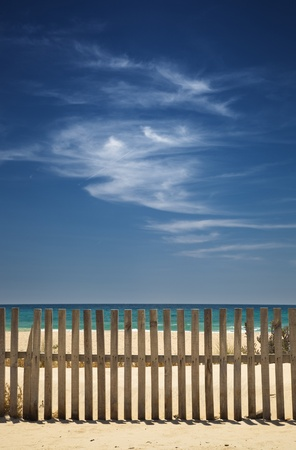 sky with clouds on the beach with a wooden fence photo