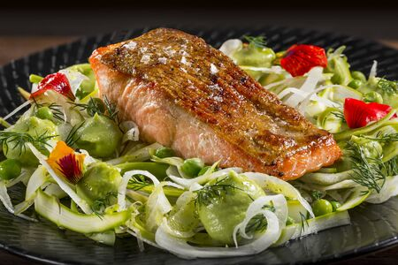 Close up of freshly grilled salmon fish fillet with avocado, peas and fennal salad garnished with rosemary and decorative flowers on a black plate