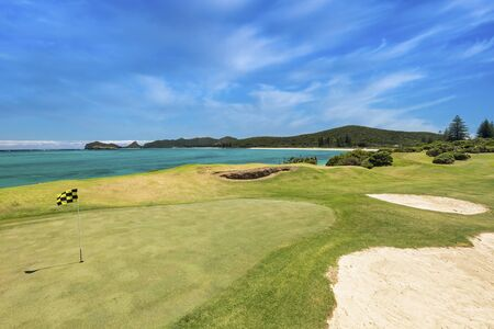 Lord Howe Island, New South Wales, Australia: November 1st 2015: Lord Howe Island Golf course, putting green yellow and black flag, with a turquoise water view and blue clear sky during a sunny day, Stock fotó