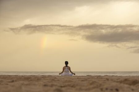 Yoga lotus pose meditation practice of young female on a beach with rainbow