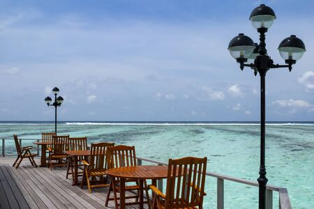 Maldives wooden cafe tables and chairs on a tropical sea, with a beautiful view of turquoise shallow water