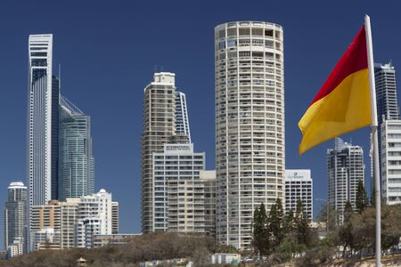 Surfers Paradise, Gold Coast, Queensland, Australia - 13 Oct 2013: Red and Yellow flag with Surfers Paradise buildings background,