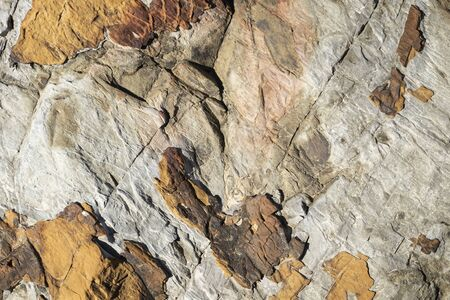 close up of brown stone rock formation texture with black cracks throughout texture background Stock Photo