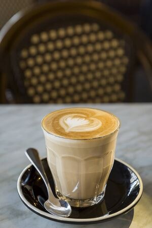 Coffee latte in glass cup with love heart shape latte art in milk froth