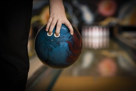 ten pin bowling ball being held in hand by bowler close up, with bowling lane and ten pins blurred in the background, copy space Banque d'images