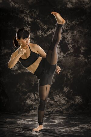 Asian female fighter performing a high roundhouse kick in studio