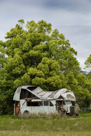 rusted, abandoned and immobile bus or truck with severe roof damage, on a field with overgrown grass, Port Stephens, New South Wales, Australia