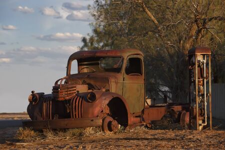 abandoned rusty old pick up truck wreck sits derelict on the side of a road on sunset