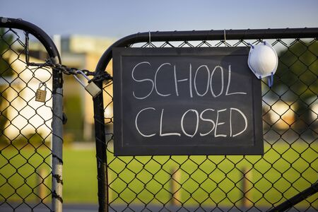 school closed sign with protective mask hanging on a padlocked gate, school closed or shutdown concept amid coronavirus fears and panic over contagious virus spread of the pandemic outbreak Standard-Bild