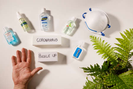 Gold Coast, Australia - March 13, 2020: coronavirus hand sanitization health hygiene concept, buckle up text, open hand with variety of gel hand sanitizers and personal face mask on white flat lay