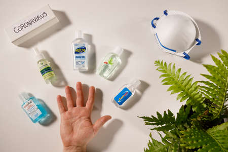 Gold Coast, Australia - March 13, 2020: coronavirus hand sanitization health hygiene concept, coronavirus text, open hand with variety of gel hand sanitizers and personal face mask on white flat lay