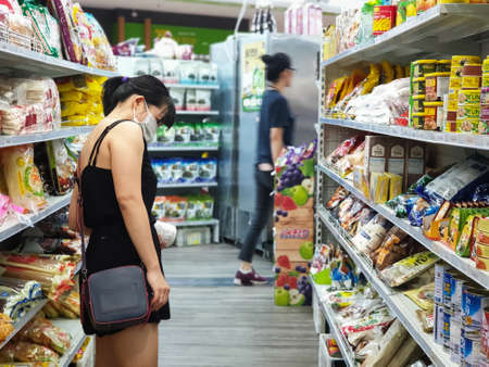 Gold Coast, Australia - March 21, 2020: Asian female wears protective medical mask in asian grocery store amid coronavirus fears, supermarket safety, health hygiene and pandemic concept, covid 19 safe