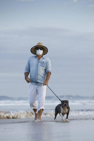 man with medical face mask walking a english blue staffy dog seaside, mans best friend, walking dog concept or staying active in a coronavirus pandemic Stock Photo