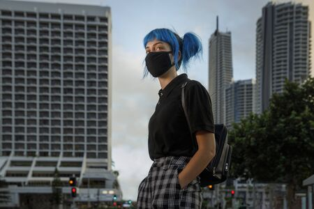 young female wearing medical mask in modern city street, stylish trendy girl with blue hair wearing fashionable protective medical mask amid coronavirus fears, covid19 pandemic, new fashion concept Stock Photo