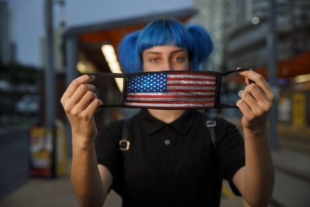 young female using american flag medical mask in city, stylish trendy girl with blue hair and united states fashionable protective medical mask amid coronavirus fears, stop covid 19 america concept