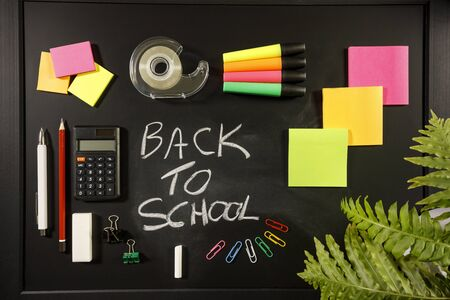 back to school concept on black flat lay, back to school written with chalk on blackboard with stationery, calculator, sticky notes, pen, pencil, paper clips, sticky tape, highlighters overhead view