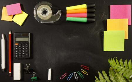 school stationary supplies on black chalkboard background with copy space ready for graphic design, school education learning concept, calculator, pen, pencil, sticky notes, tape, highlighters, chalk