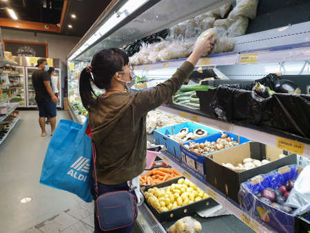 Gold Coast, Australia - April 29, 2020: Asian female wears protective medical mask in asian grocery store amid coronavirus fears, supermarket safety, health hygiene and pandemic concept, covid 19 safe Editorial