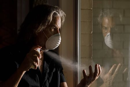 coronavirus male medical mask sanitizer concept, reflection of middle aged man in protective mask spraying hand sanitizer at home in self isolation quarantine covid-19 virus pandemic crisis prevention