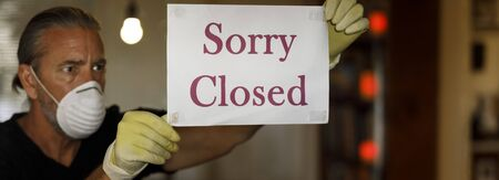 cornavirus closed for business concept, male business owner with medical mask puts sorry closed sign on window during covid 19 virus pandemic, cafe shop bankrupt, covid-19 restrictions and lockdowns