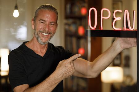 open for business concept, small business owner reopening premises after covid-19 virus pandemic, happy man pointing to red neon open sign at a bar restaurant or cafe window after coronovirus lockdown Stock Photo