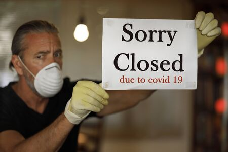 coronavirus closed for business concept, male business owner with medical mask puts sorry closed sign on window during covid 19 virus pandemic, cafe shop bankrupt, covid-19 restrictions and lockdowns