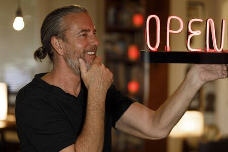 open for business concept, small business owner reopening premises after covid-19 virus pandemic, happy man looking at red neon open sign at a bar restaurant or cafe window after coronovirus lockdown