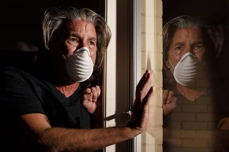 coronavirus crying male medical mask quarantine, self isolation concept, depressed distraught mans reflection in window with tears wearing protective mask. covid-19 virus pandemic, healthcare crisis Stock Photo