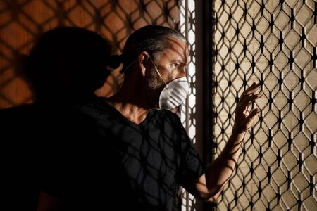 coronavirus male medical mask quarantine, self isolation concept, frustrated middle aged man wearing protective mask at home looking outside front door, covid-19 virus pandemic, healthcare crisis Stock Photo
