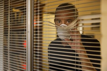 coronavirus, male wearing medical mask in self isolation looking out of window blinds of home. Worried man takes Covid 19 quarantine safety measures for protection against the corona virus pandemic Stock Photo