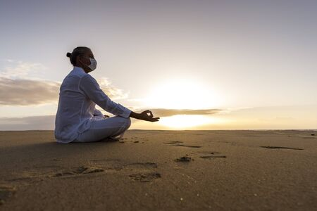 meditating man in medical mask in lotus pose on the beach, male wearing surgical face mask and white yoga clothes with man bun top knot hairstyle sitting in a meditation pose on an empty beach sunrise