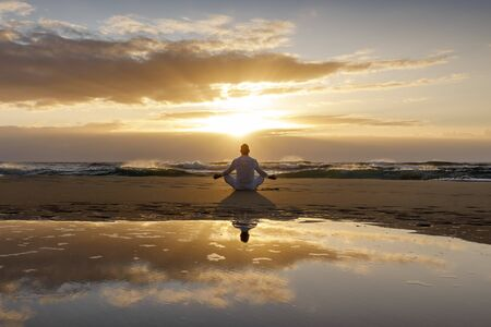 yoga meditation silhouette lotus sunrise beach, mindfulness, wellness and wellbeing concept, water reflection of man in yoga lotus pose sitting alone on sand with ocean cloud background, copy space