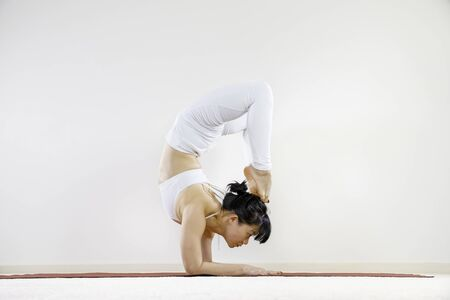 young asian yoga girl doing scorpion pose, advanced yoga inversion concept, side view of flexible yogi practicing Vrischikasana forearm balance with white sportswear and white background copy space