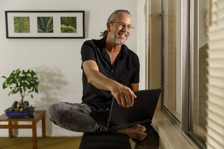 working or remote learning from home concept, man wearing glasses and in casual clothes, smiling using laptop by a window at his home office