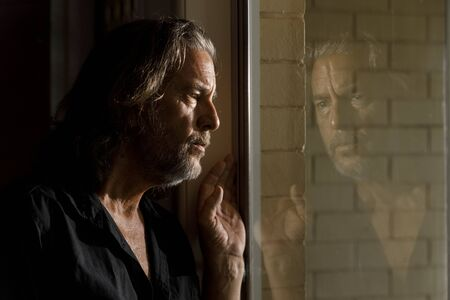 man in self isolation, stay home concept, thinking mans reflection in glass window of brick house, concerned long haired male with beard looking through window Stock Photo