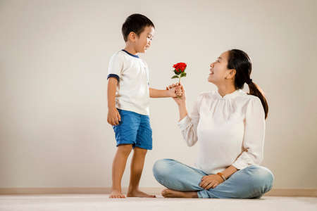 Asian mother and child holding rose. Vietnamese boy gives parent a red rose flower as a loving gesture. happy mum and son or mothers day concept