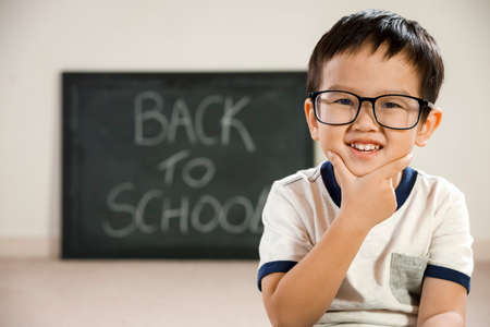 Smiling asian boy with school blackboard behind, back to school education concept, intelligent happy vietnamese student with glasses on and hand on chin thinking pose, chalkboard with text background Stock Photo