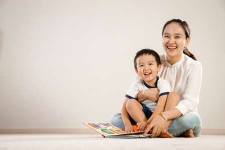 Asian mother and child reading book together concept. Vietnamese mum and son sitting on floor, laughing while flipping pages of a story book, white background Stock Photo