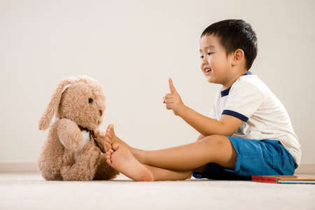 Asian boy talking to teddy bear, Vietnamese toddler pointing and speaking to stuffed toy, cute kid sitting on floor communicating with his favorite toy friend Stock Photo