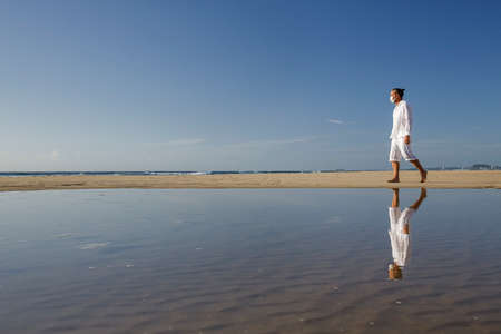 man with medical mask walking on beach during coronavirus covid 19 pandemic, social distance concept, male exercising wearing face mask for protection against virus, ocean background Stock Photo