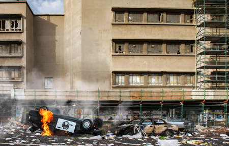 American riots and protests cause vandalism, looting and destruction, riot aftermath concept, upturned police car smashed on fire, broken windows of abandoned building, total anarchy and lawlessness