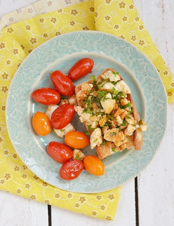 scramble:  bruschetta with herby tofu scramble,and grilled  cherry tomatoes Stock Photo