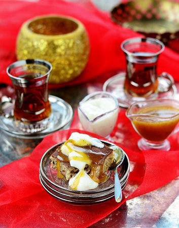 dates pudding with caramel sauce on glass plate photo