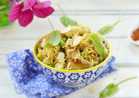 pakistani food: pilaf with chicken, peas and almonds in a ornamental bowl