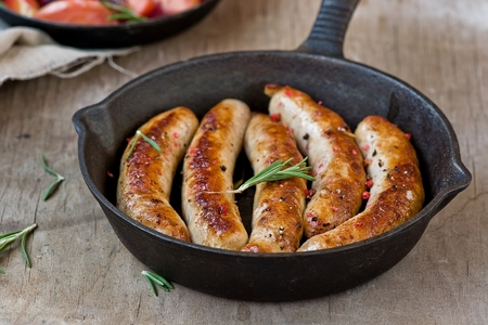 fried sausages on a frying pan on a wooden background Reklamní fotografie