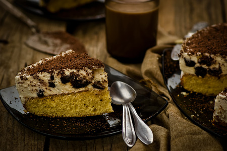 cheesecake with prunes and chocolate cut on pieces on a wooden table. photo