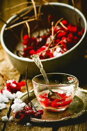 guelder rose berry: fresh berries of a guelder-rose in a glass cup on a wooden table. style rustic.  the image is tinted